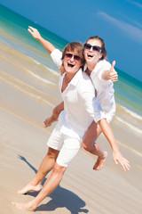 couple piggybacking cheerful on beach