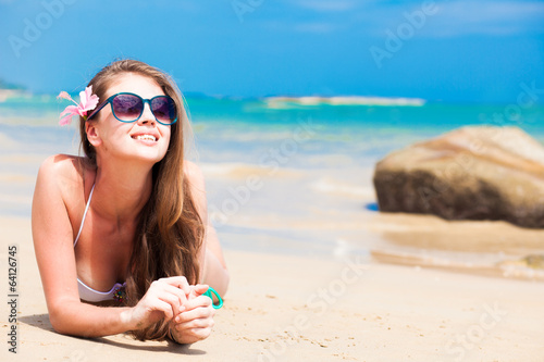 long haired girl in bikini and sunglasses on tropical beach
