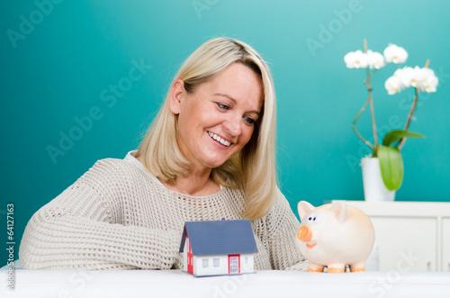 frau mit sparschwein und miniaturhaus