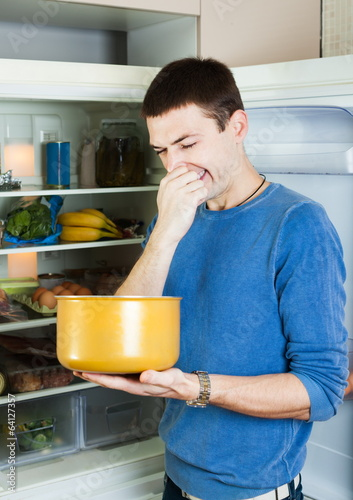 Hungry man holding his nose