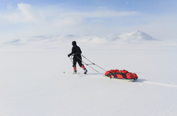 Crosscountry skier with pulka in Sweden.