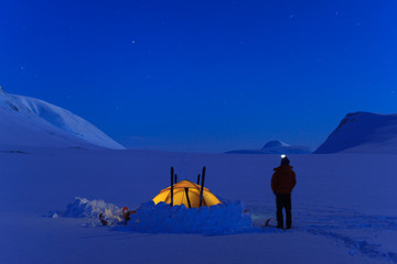 Tent in the snow during a night in Lapland.