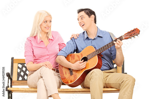 Man playing guitar for a girl seated on bench