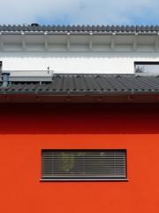 Passivhaus mit roter Fassade und Fenster mit Jalousie