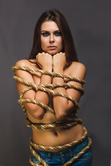 brunette hostage, captive woman bound with rope prisoner in jean