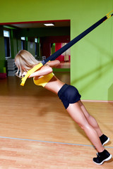 Beautiful young woman illustrating TRX work out