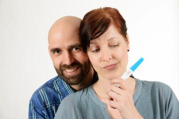 Lachender Mann und zweifelnde Frau mit Schwangerschaftstest