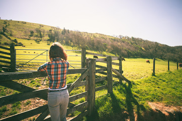 Young woman by a fence on a ranch