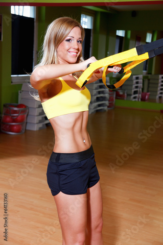 Beautiful young woman doing exercise in the gym