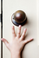 Kid's hand reaching up for the door knob to open it