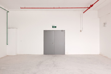 Interior of a bare, empty room with the door and exit sign