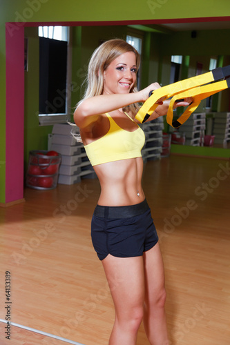 Beautiful young woman doing TRX exercise in the gym