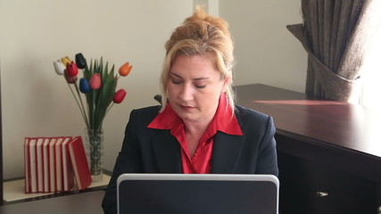 Businesswoman using laptop and writing