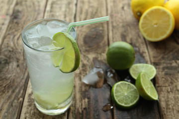 Fresh drink with lime and ice on wooden table