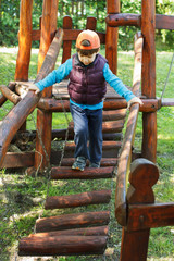Little boy in cap walking on jungle gym