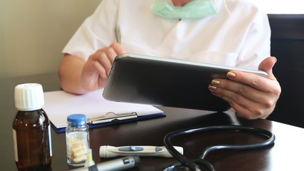 Female doctor working with digital tablet in office