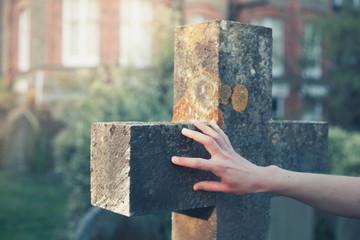 Hand touching a gravestone