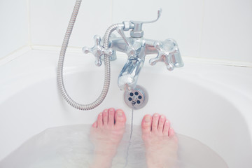 The feet of a young woman in a bathtub