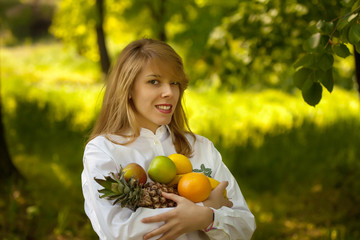 girl in the park holding fruit in her arms