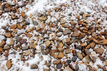 крупная и мелкая галька посыпана снегом