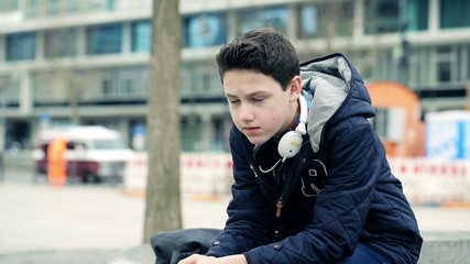 Sad, pensive young teenager sitting in the city