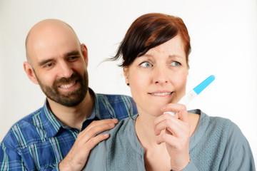 Glücklicher Mann und ängstliche Frau mit Schwangerschaftstest