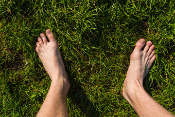 male bare feet on the meadow