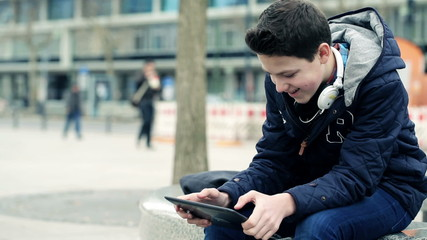 Young teenager playing game on tablet computer in the city