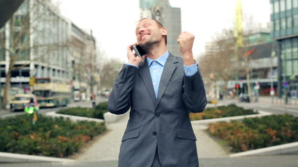 Successful businessman hearing great news on the phone