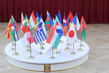 White table with 28 national flags at the conference