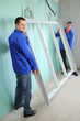 Two men in jackets holding a new window frame