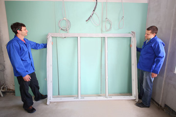 Two men with the new window frame