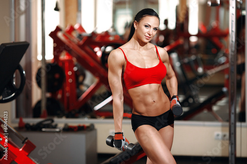 Girl with perfect body with dumbbells in the gym