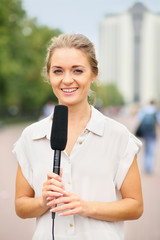 Girl reporter in white blouse and with a microphone