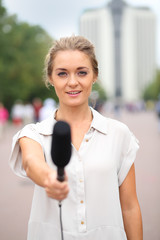 Professional reporter beautiful girl standing on the street