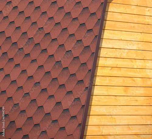 Wooden house wall and part of red roof from soft tile closeup