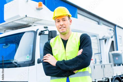 Kranfahrer vor Kranwagen einer Baustelle