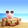 Suitcase with piggy bank in sunglasses on tropical beach - 64147347