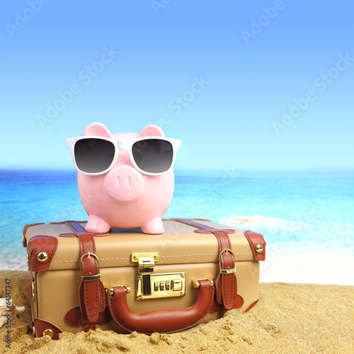 Suitcase with piggy bank in sunglasses on tropical beach