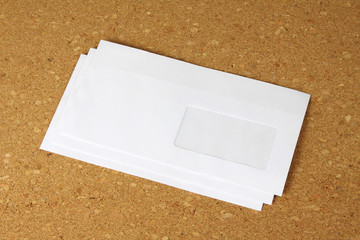 white envelope on corkboard background.