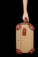 Hand holding travel suitcase isolated on black