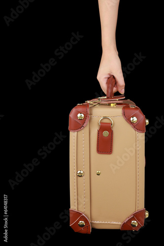 Hand holding travel suitcase isolated on black