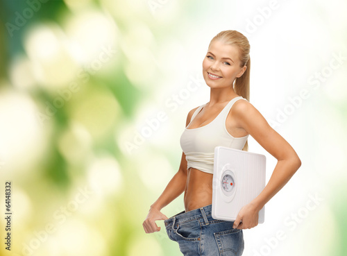 smiling woman showing big pants and holding scales