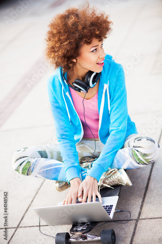 Funky woman sitting on skateboard with laptop