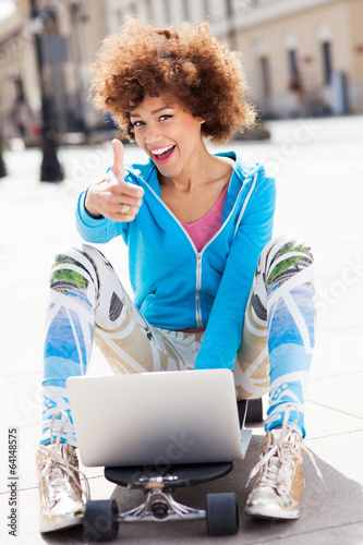 Urban woman with laptop and thumbs up
