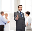 handsome buisnessman showing thumbs up in office
