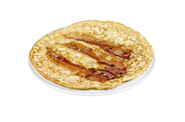 A plate with a pancake with bacon strips on a white background.