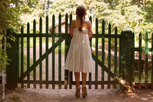 Girl standing on tiptoes and looking over the fence
