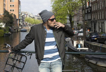 cool guy smoking on a bridge in Amsterdam