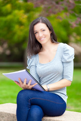 Young beautiful female student reading a book